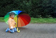 Toddler girl with  umbrella in rainbow colors