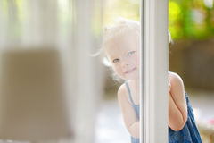 Cute little toddler girl peeking into a window. On beautiful warm and sunny summer day Royalty Free Stock Images