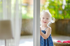Cute little toddler girl peeking into a window. On beautiful warm and sunny summer day Royalty Free Stock Photo