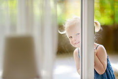 Cute little toddler girl peeking into a window Stock Photography