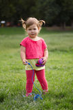 Cute Little toddler girl in pink dress playing in park in front of green grass Royalty Free Stock Images