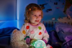 Cute little toddler girl playing with colorful night light lamp before going to bed. Sleepy tired baby daughter in. Nightwear having fun. Healthy child not stock photography