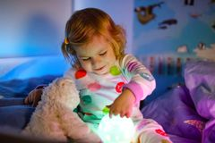 Cute little toddler girl playing with colorful night light lamp before going to bed. Sleepy tired baby daughter in. Nightwear having fun. Healthy child not royalty free stock image