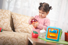 Cute little toddler girl playing with toy in room, Child and toy royalty free stock photo