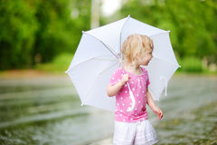 Cute little toddler girl on a rainy summer day Stock Image