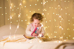 Cute little toddler girl reading book in dark room with Christmas lights royalty free stock images