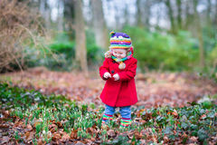 Cute little toddler girl in red coat in autumn park Royalty Free Stock Images