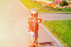 Cute little toddler girl riding scooter in the Royalty Free Stock Photography