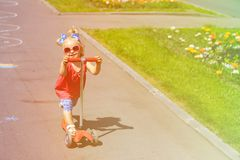 Cute little toddler girl riding scooter in the Stock Image