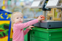 Cute little toddler girl shopping in a food store Stock Photos