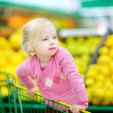 Cute little toddler girl shopping in a food store Royalty Free Stock Images