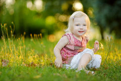 Cute little toddler girl sitting on the grass Royalty Free Stock Photo