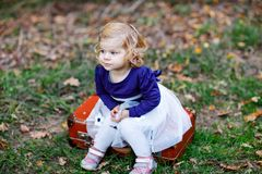 Cute little toddler girl sitting on suitcase in autumn park. Happy healthy baby enjoying walking with parents. Sunny stock photos