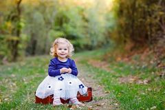 Cute little toddler girl sitting on suitcase in autumn park. Happy healthy baby enjoying walking with parents. Sunny stock photo