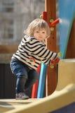 Cute little toddler girl almost sliding down the children`s slide stock photo
