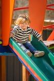 Cute little toddler girl sliding down the children`s slide royalty free stock photos