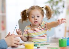 Cute little toddler girl in striped shirt and pony tails paints in the art class royalty free stock photos