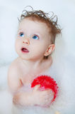 Cute little toddler girl taking a bath with bubbles. Cute little blond toddler girl taking a bath with bubbles and foam Royalty Free Stock Images
