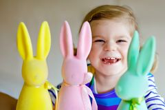 Cute little toddler girl with three colored pastel bunnies Happy baby child having fun with Easter decorations bunny in. Pink, yellow and green. Adorable stock photos