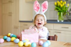 Cute little toddler girl wearing Easter bunny ears playing with colored pastel eggs. Happy baby child unpacking gifts. Adorable healthy smiling kid in pink stock photos
