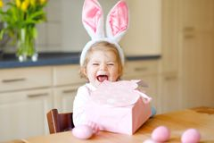 Cute little toddler girl wearing Easter bunny ears playing with colored pastel eggs. Happy baby child unpacking gifts royalty free stock photos