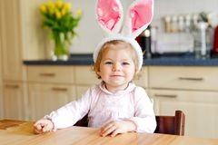 Cute little toddler girl wearing Easter bunny ears playing with colored pastel eggs. Happy baby child unpacking gifts. Adorable healthy smiling kid in pink stock images