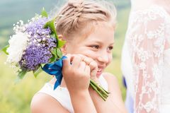 A cute little touching child and an amazing wedding bouquet of white and purple peonies at her parents` wedding. A cute little touching girl and an amazing white stock images