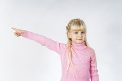 Cute little towhead girl showing to white sheet Stock Photography