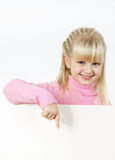 Cute little towhead girl showing to white sheet royalty free stock photo