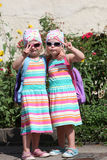 Cute little twin girls making V-signs Stock Images