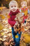 Cute little twins looking at falling down autumnal leaves. Cute, little twins looking at falling down autumnal leaves stock photo