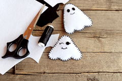 Cute little white ghosts crafts, felt sheets, scissors, thread, needles on an old wooden background. Easy Halloween felt pattern Stock Photo