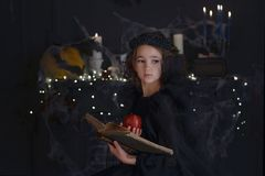 Cute little witch child girl in halloween costume and decorations. Royalty Free Stock Image