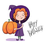Cute little witch holding a big pumpkin and smiling Royalty Free Stock Photography