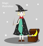Cute little witch with a magic wand in a hat and cloak with stars, the chest with the stars and the moon, gray background Stock Image