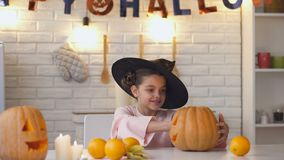 Cute little witch sitting at Halloween party with jack pumpkin showing thumbs-up