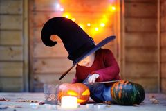 Cute little wizard with magic wand and jack-o-lanterns Stock Photography