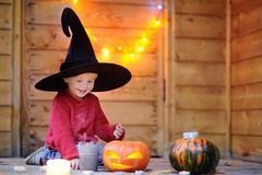 Cute little wizard with magic wand and jack-o-lanterns Stock Photo