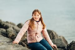Cute little 9-10 year old girl playing by the lake on a cold day. Wearing warm pink padded jacket Royalty Free Stock Photography