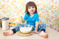 Cute little 2 years boy cooks sitting on a table at home kitchen Stock Photos