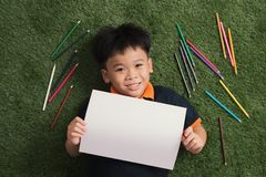Cute little 7 years boy drawing in park outside lying on the grass royalty free stock photos