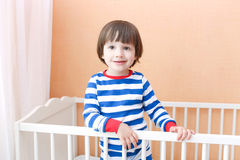 Cute little 2 years child standing in bed at home Stock Image