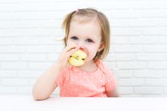 Cute little 2 years girl with apple at home stock image
