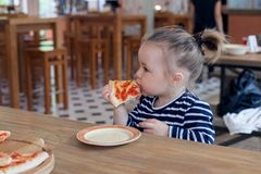 Cute little 2 years girl eating pizza in the restaurant. stock image