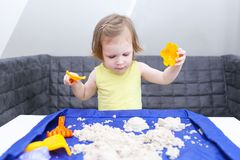 2 years girl plays kinetic sand at home. Cute little 2 years girl plays kinetic sand at home Stock Image