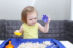 Cute little 2 years girl plays kinetic sand at home. Little 2 years girl plays kinetic sand at home Royalty Free Stock Photography
