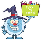Cute Little Yeti Character With Witch Hat Holding Up A Trick Or Treat Halloween Candy Basket. Cute Little Yeti Cartoon Mascot Character With Witch Hat Holding Up Stock Photo