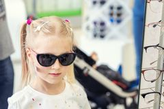 Cute little young caucasian blond girl trying on and choosing sunglasses in front of mirror at optic eyewear store. Adorable. Schoolgirl child having fun bying stock image