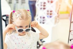 Cute little young caucasian blond girl trying on and choosing sunglasses in front of mirror at optic eyewear store. Adorable. Schoolgirl child having fun bying royalty free stock photography