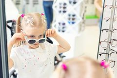 Cute little young caucasian blond girl trying on and choosing sunglasses in front of mirror at optic eyewear store. Adorable. Schoolgirl child having fun bying royalty free stock photos
